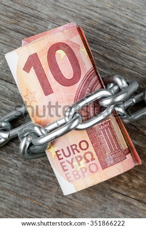 Ten euro bills with chain , concept money tied up - stock photo