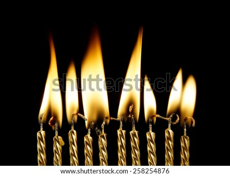 Ten golden burning birthday candles on black background  - stock photo