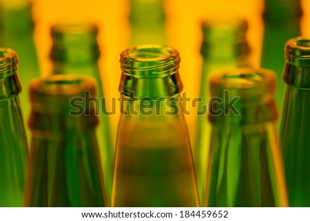Ten green empty beer bottles shot with orange light.