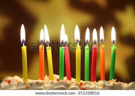 Ten lit birthday candles close up, shallow dof