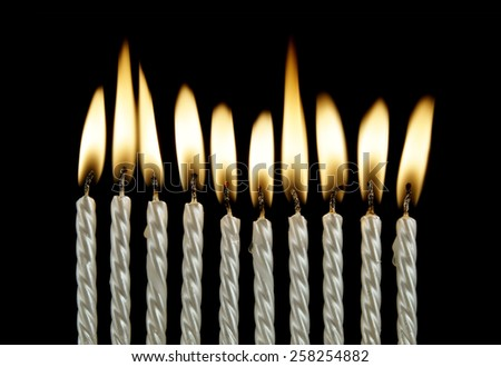 Ten silver burning birthday candles on black background  - stock photo