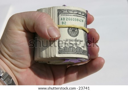 Ten Thousand Dollars rolled up with yellow rubber band, handing it to YOU the viewer! - stock photo