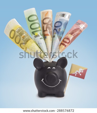 Ten,twenty,fifty,one hundred and a 200 Euro banknote in a smiling piggybank of Bhutan.(series) - stock photo