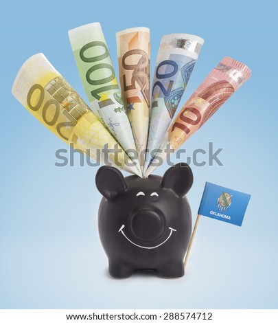 Ten,twenty,fifty,one hundred and a 200 Euro banknote in a smiling piggybank of Oklahoma.(series) - stock photo