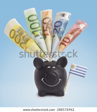 Ten,twenty,fifty,one hundred and a 200 Euro banknote in a smiling piggybank of Uruguay.(series) - stock photo