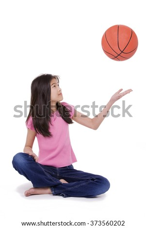 Ten year old Asian girl sitting on floor throwing basketball up in the air, isolated on white - stock photo