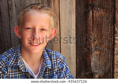Ten year old boy with a barn wood background. - stock photo