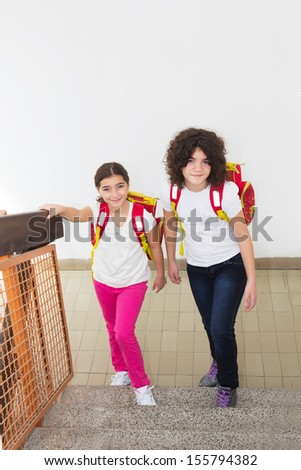 Ten year old twin sisters go to school - stock photo