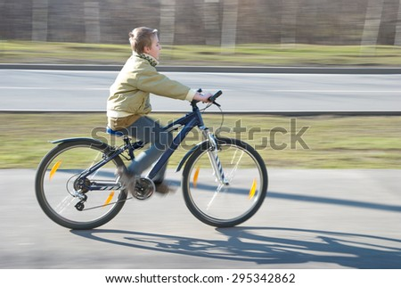 Ten years old boy rides bike on bicycle path in springtime - stock photo