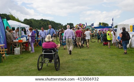 Tenbury Wells, Herefordshire, UK - August 3rd 2013. Lady wearing sun hat in a motorized wheelchair joining the crowds at the Tenbury agricultural show in Herefordshire in the UK.  - stock photo