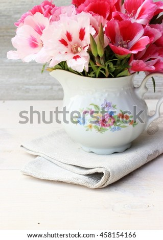 Tender beautiful bouquet of pink flowers in a small vintage porcelain pincher decorated with floral pattern. Floral decor element in a rustic setting. Full light white composition