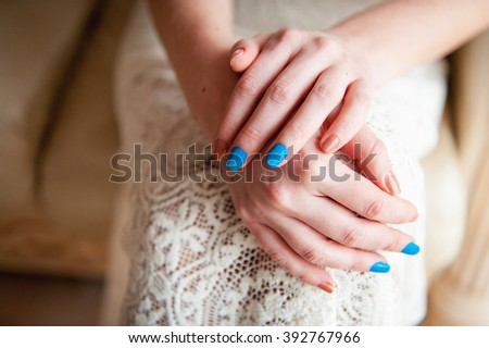 Tender beautiful bride's hands on elegant white lace wedding dress closeup. - stock photo