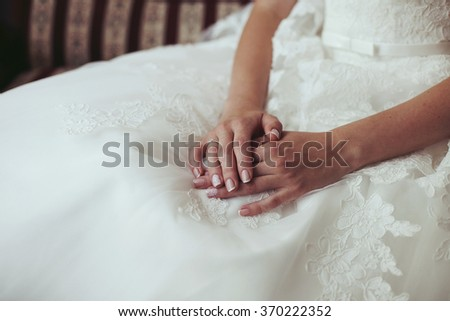 Tender beautiful bride's hands on elegant white wedding dress closeup - stock photo