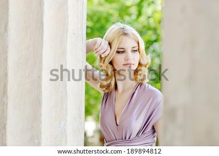 tender beautiful girl  standing near the column - stock photo