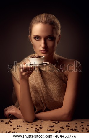 Tender beautiful woman holding coffee cup and beans over dark gradient background - stock photo