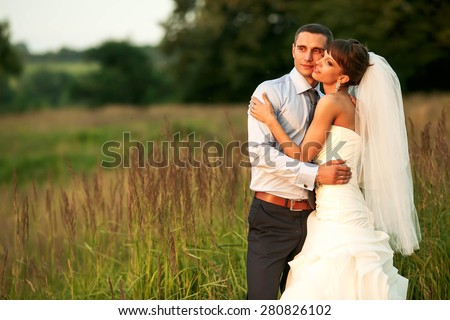 tender couple is posing in the herbs on the background forest - stock photo