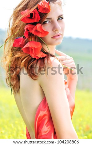 tender lady standing with poppies in her hair - stock photo