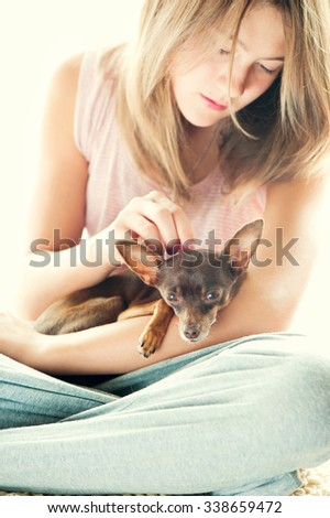Tender love. Young girl in pyjamas holding and stroking her lovely Toy-terrier dog in morning rays of sunlight. Multicolored vibrant vertical indoors image. - stock photo