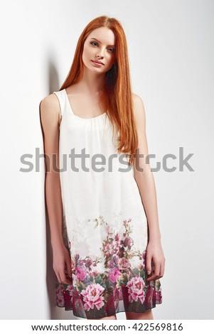 Tender portrait of beautiful redhead female wearing sleeveless flower print summer dress posing leaning against white wall - stock photo