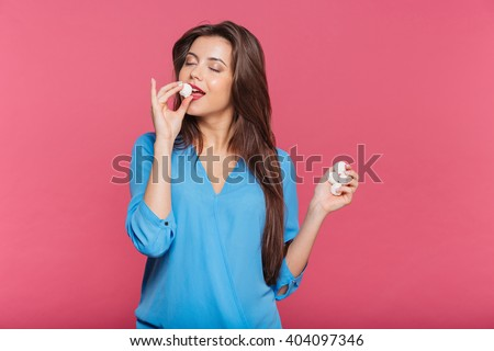 Tender pretty young woman with eyes closed eating sweet candies over pink background - stock photo