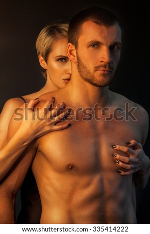 Tender romantic young lovers holding each other in a close intimate embrace , view from behind the bare back of the man - stock photo