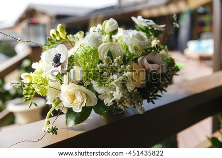 Tender white bouquet with greenery stands on wooden porch