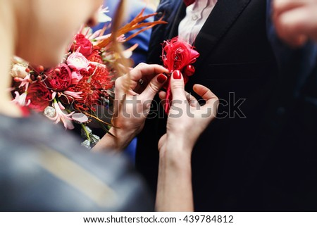 Tender woman's hands piut a boutunniere on black jacket