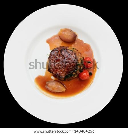 Tenderloin steak in plate, isolated on black background - stock photo