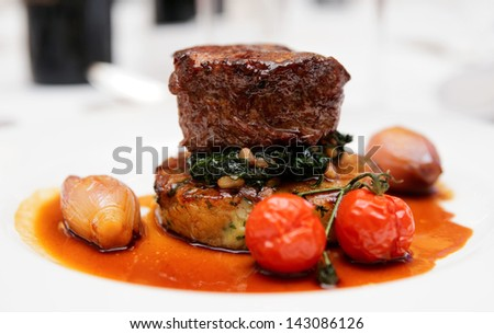 Tenderloin steak with spinach, sweet onions and cherry tomatoes - stock photo