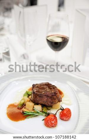 Tenderloin steak with wine on restaurant table - stock photo