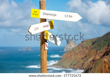 Tenerife, Canary Islands, Spain - December 23, 2015: Road table with sign directions to Chamorga, Almaciga and El Draguillo villages with rocky coastline on the background.