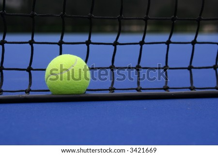 Tennis ball against the net on a blue court
