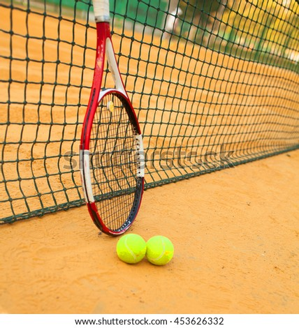 Tennis Ball and Racket on clay court - stock photo