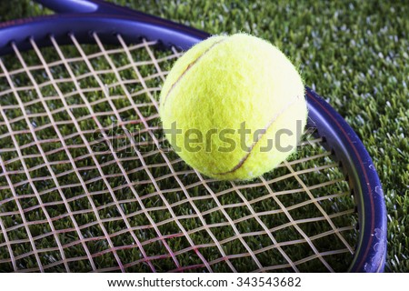 Tennis ball and racket over green grass, horizontal image