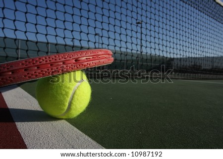 Tennis ball and racquet on a court - stock photo
