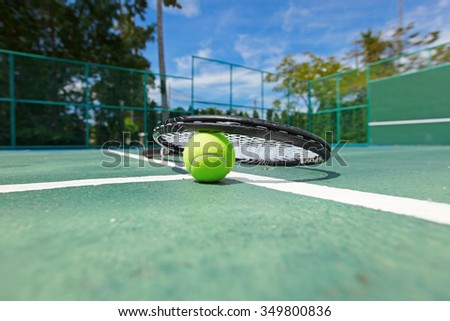 Tennis ball and racquet on the court close-up - stock photo