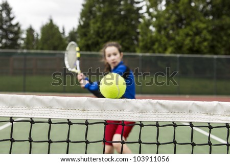 Tennis ball barely clearing the net with female player rushing to net - stock photo