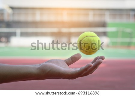 Tennis ball floating in the air above hand. blur tennis court background