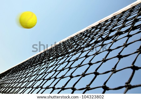 Tennis  ball flying over the net under the blue sky. - stock photo