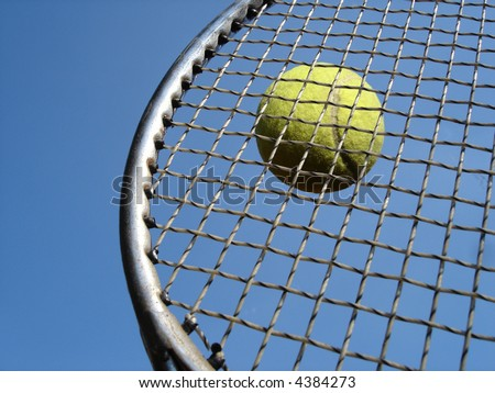Tennis ball hitting racket against blue sky. - stock photo