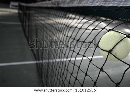 Tennis ball in net - stock photo