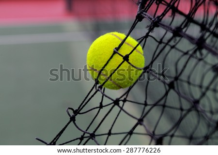 Tennis ball in net at tennis court