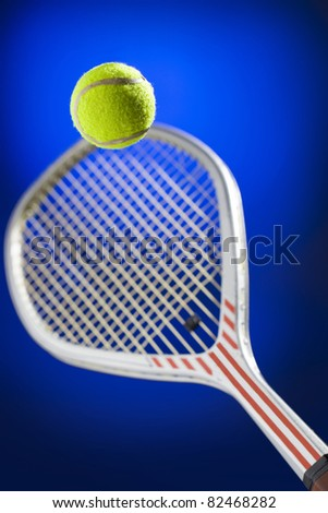 Tennis ball just about to be hit from the tennis racket on blue background - stock photo