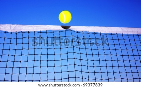 Tennis Ball just over the Net - stock photo