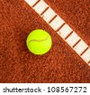Tennis ball next to line on a tennis clay court - stock photo