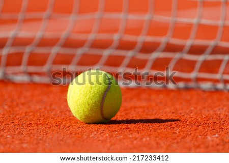Tennis ball on a court near a sport net - stock photo