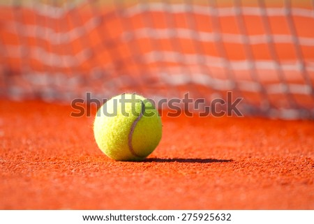Tennis ball on a orange hard court 