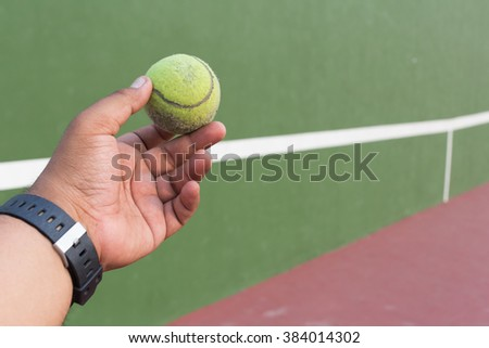 Tennis ball on my hand in a court.