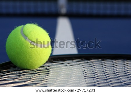 Tennis ball on racket strings - stock photo