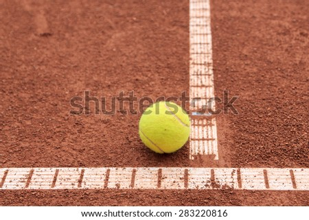 Tennis ball on the clay tennis court - stock photo